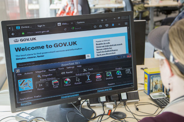 A low vision user's computer set up: large monitor at low resolution showing GOV.UK in browser with personalised colour settings. ZoomText preference panel is visible.