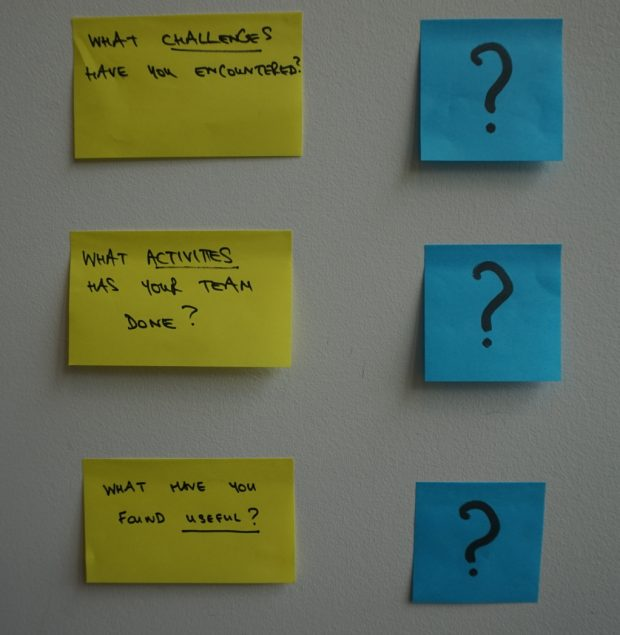 displaying three post-it notes with three questions: What challenges have you encountered?, What activities has your team done?, What you found useful?