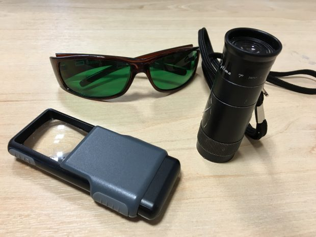 A Magnifying glass,, monocular and sunglasses with a special green tinted eye shields