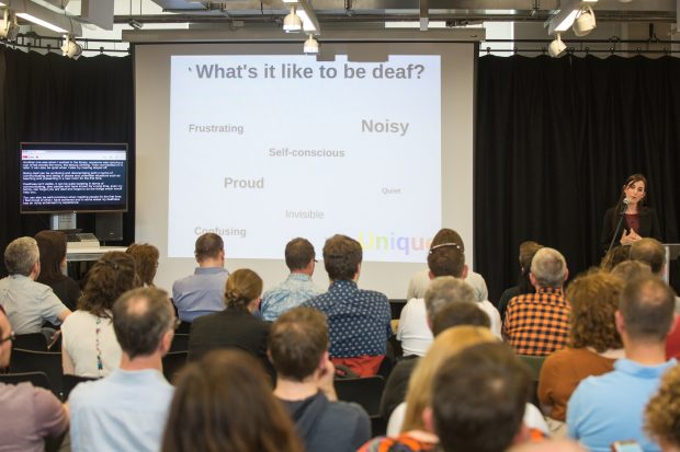 An audience listening to a talk with a slide saying 'what it's like to be deaf' in the background