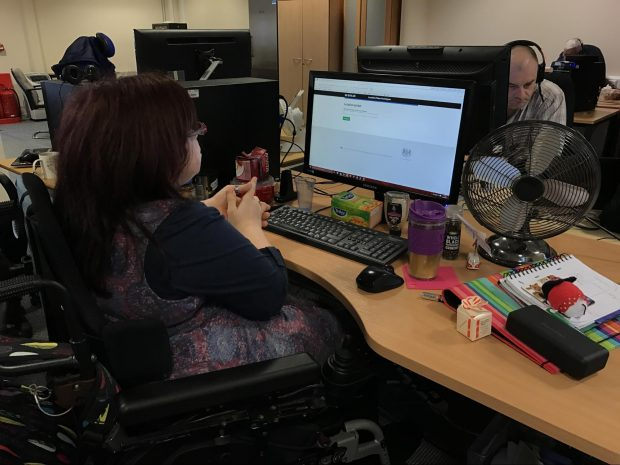 A photo of Becs sat in front of a computer. She is sat in a wheelchair with her hands clasped together.
