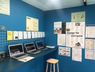 Three Chrome laptops on a long desk with a stool underneath, posters on two surrounding with headings of Vision and Design for Everyone.