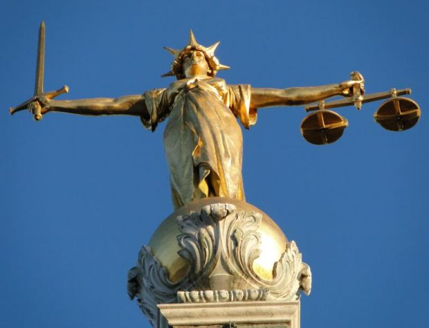 Gold statue Of 'Justice', Central Criminal Court, Old Bailey, London viewed from a low angle against a blue sky.