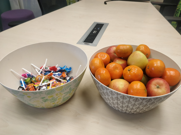 2 colourful bowls on a desk containing fruits (apples and satsumas) and sweets