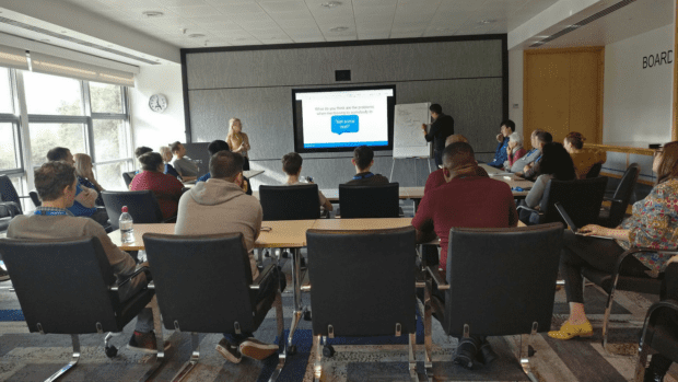 A room of people watching a presentation with one presenter looking at a large screen and the other writing on a piece of paper stuck to a whiteboard.